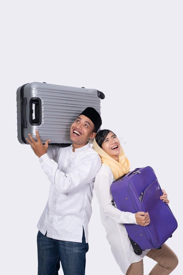 Pares musulmanes emocionados con la maleta en el fondo blanco foto de archivo