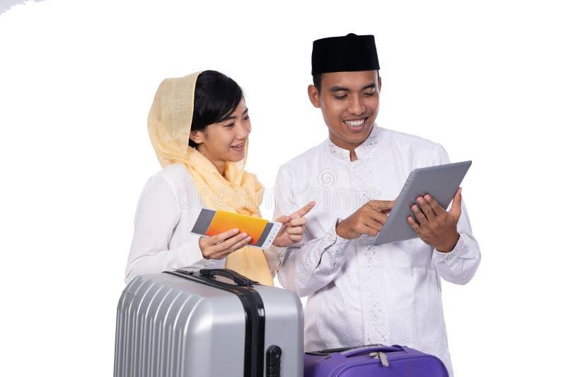 Pares musulmanes usando la PC de la tableta antes de viajar fotografía de archivo libre de regalías