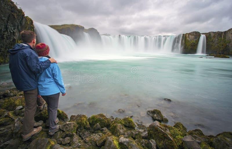 Pares na cachoeira de Goðafoss, Islândia imagens de stock