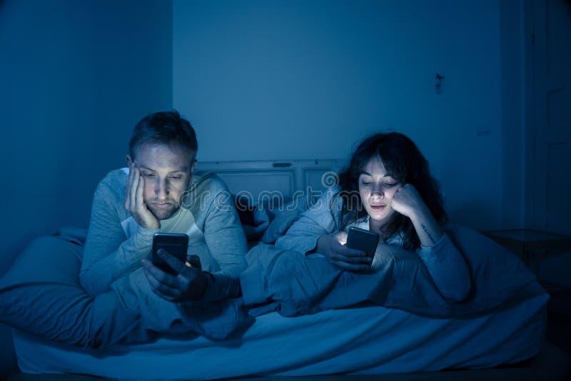 Pares na cama nos telefones espertos que ignoram-se no relationshi foto de stock