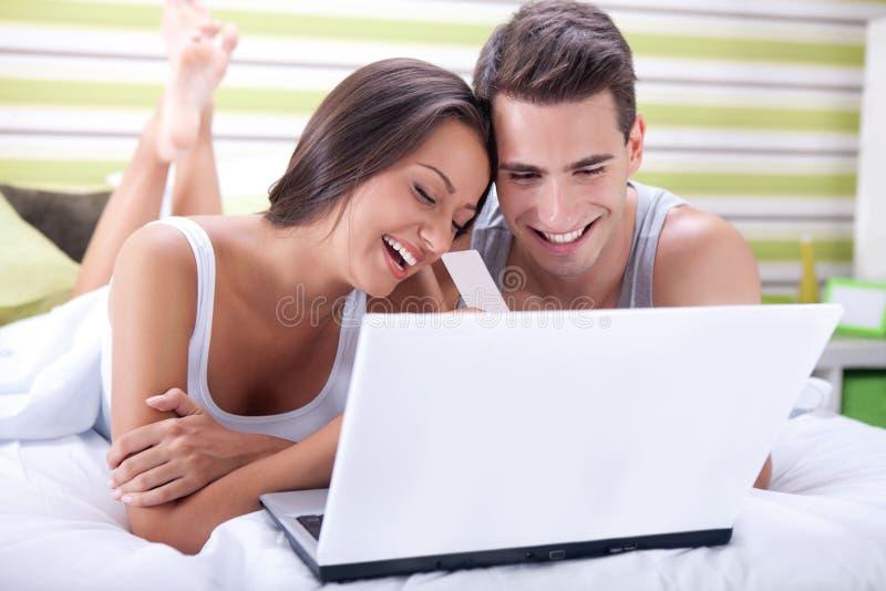 Pares na cama que compra em linha com cartão de crédito imagens de stock
