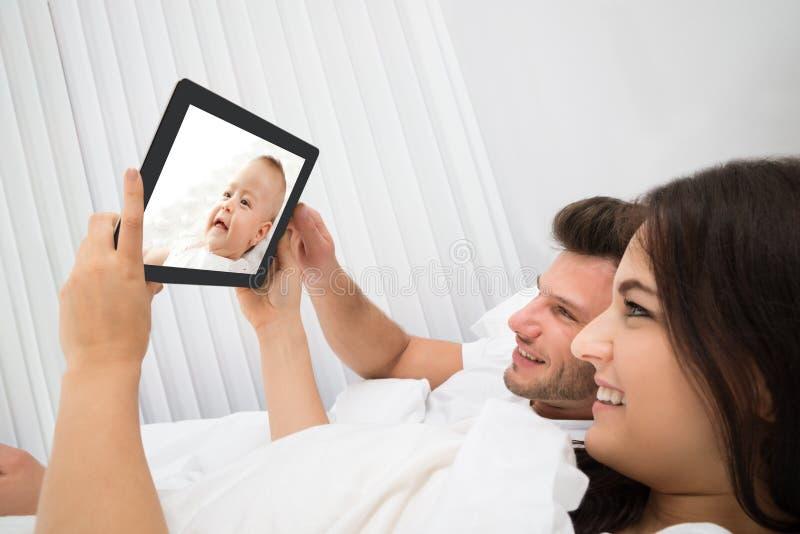 Pares na cama que olha o bebê na tabuleta digital fotos de stock