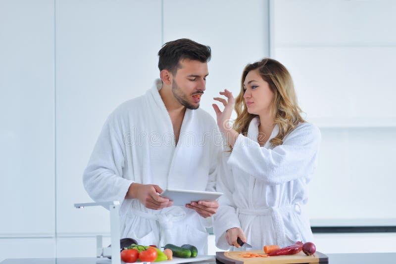 Pares na cozinha home usando a tabuleta eletrônica fotos de stock royalty free