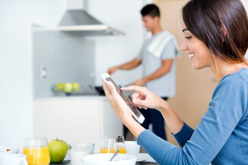 Pares na cozinha que prepara o café da manhã e o Internet da consultação foto de stock