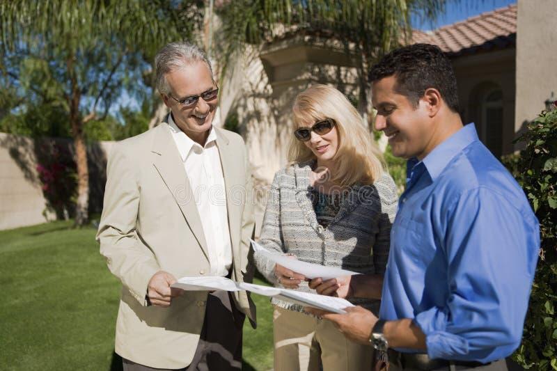 Pares na discussão com mediador imobiliário imagens de stock