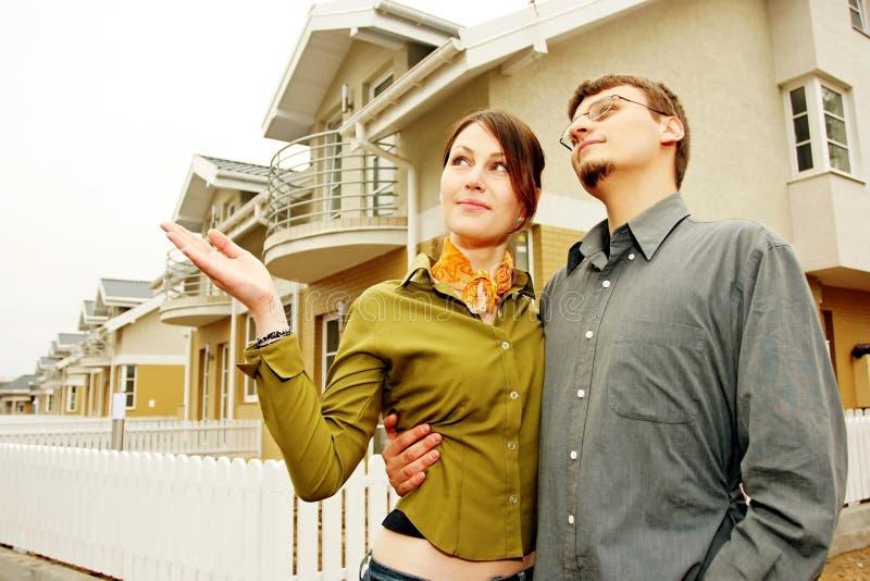Pares na frente da casa one-family fotografia de stock