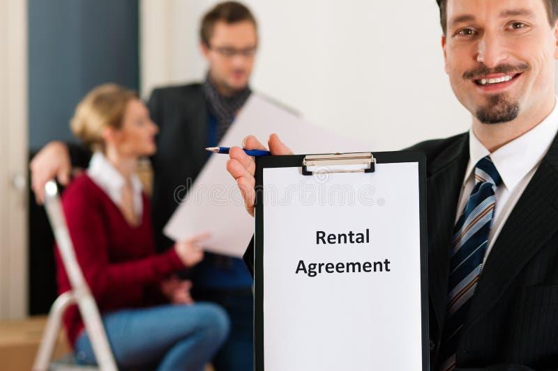 Pares na HOME com o corretor de bens imobiliários imagem de stock royalty free