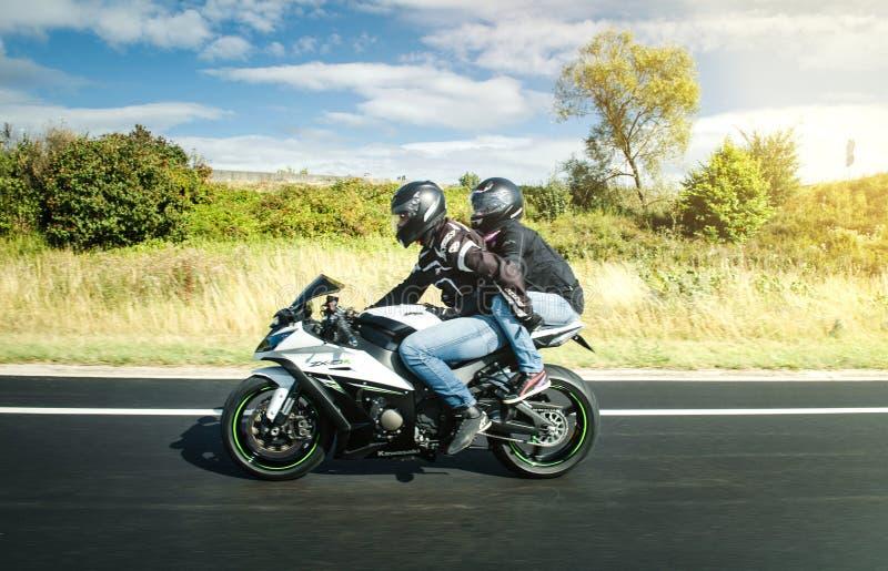 Pares na motocicleta muito rápido na estrada francesa imagens de stock royalty free