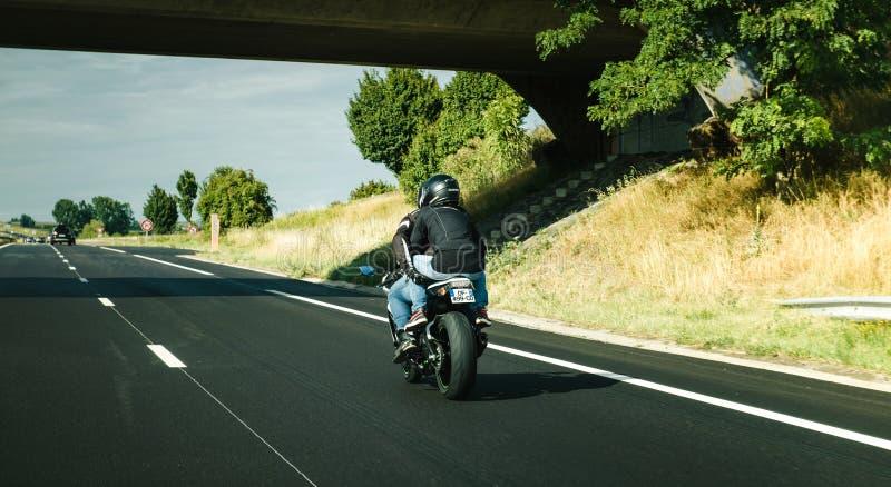 Pares na motocicleta muito rápido na estrada francesa fotos de stock
