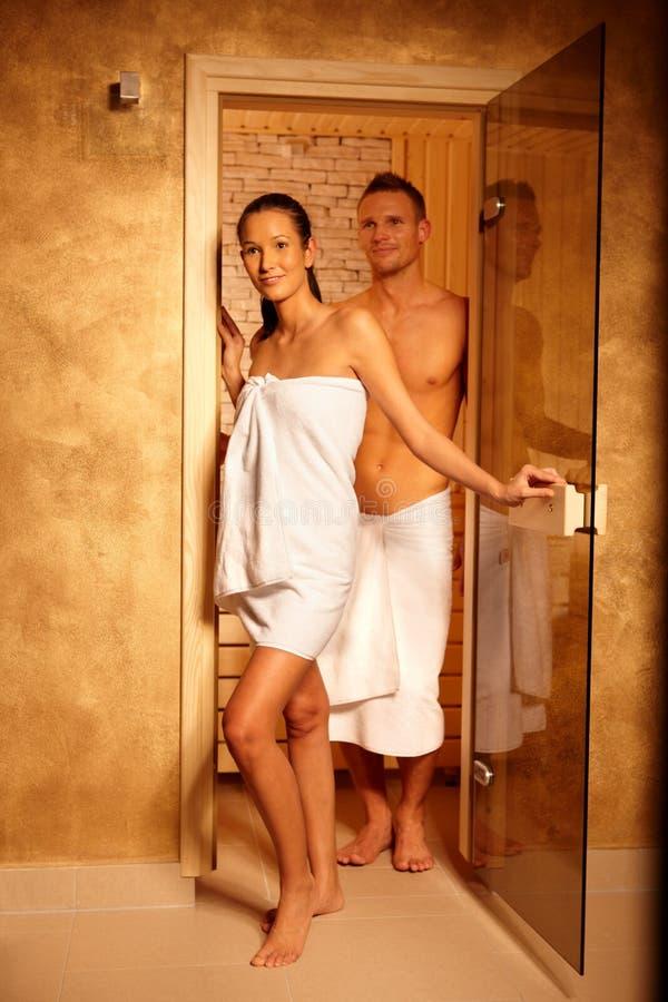 Pares na porta da sauna imagens de stock royalty free