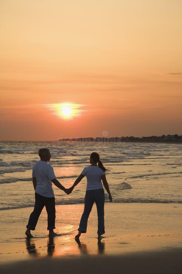 Pares na praia em mais sunsest. fotografia de stock