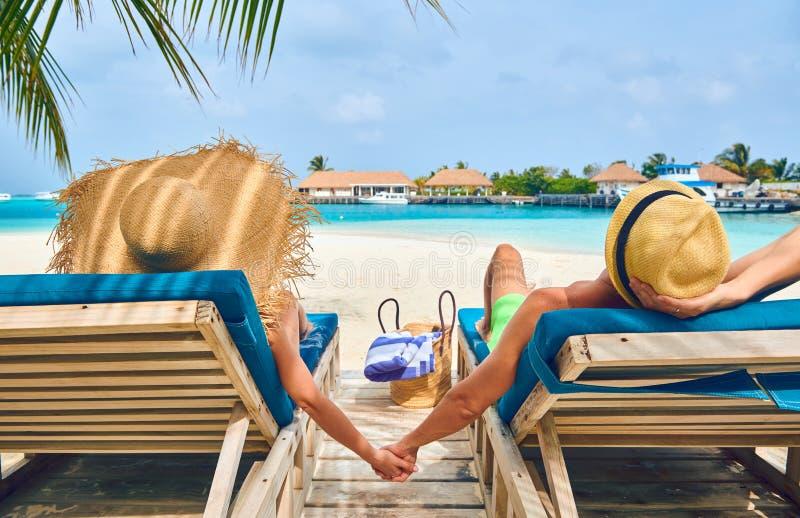 Pares na praia em vadios de madeira da cama do sol imagem de stock royalty free