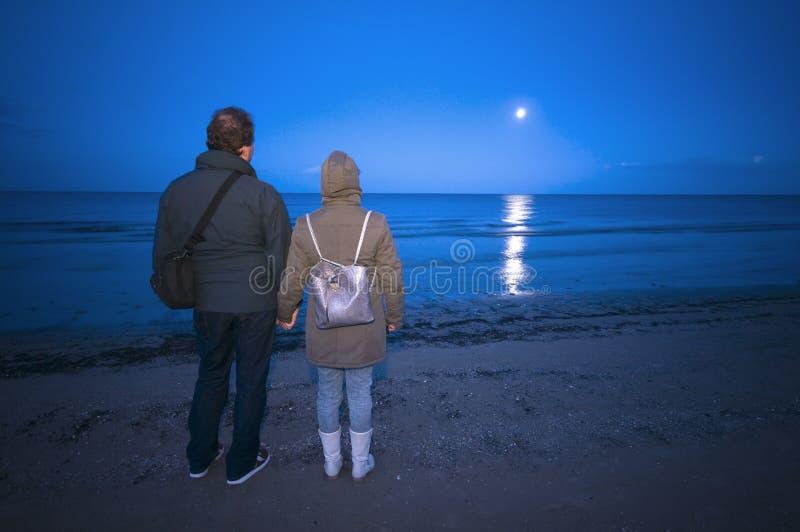 Pares na praia na noite foto de stock royalty free