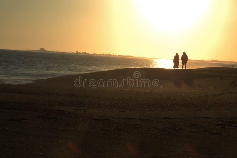 Pares na praia no por do sol fotografia de stock royalty free
