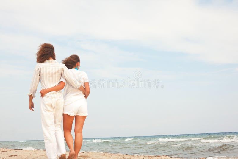 Pares na praia que aprecia as férias imagens de stock royalty free