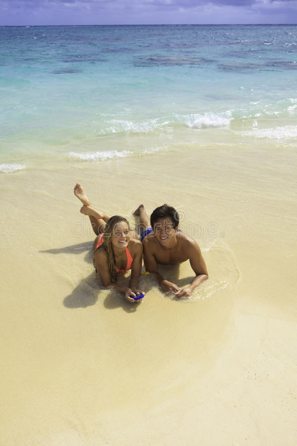 Pares na praia que texting foto de stock