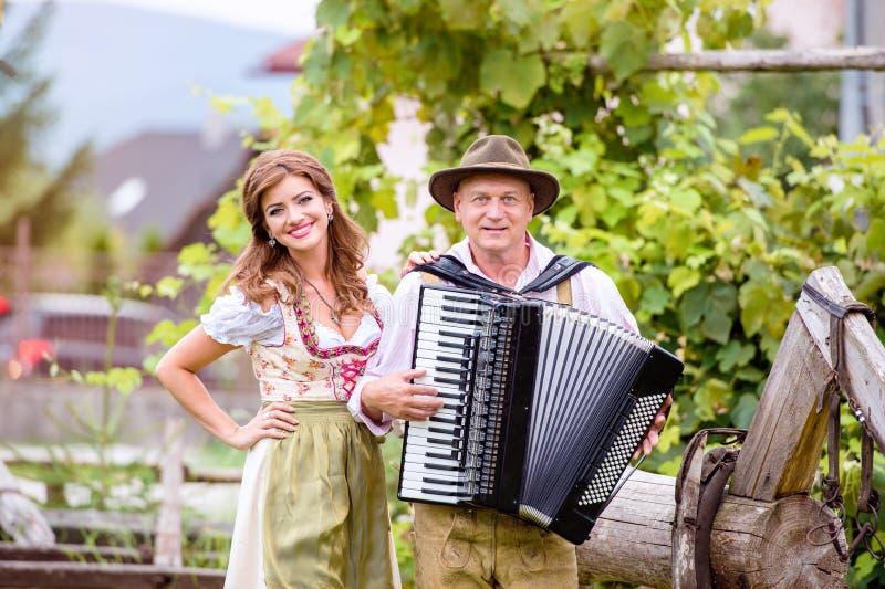 Pares na roupa bávara tradicional com acordeão, peixe-agulha verde fotos de stock royalty free