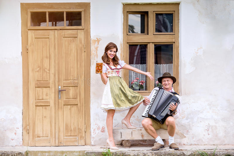 Pares na roupa bávara tradicional com cerveja e acordeão fotografia de stock