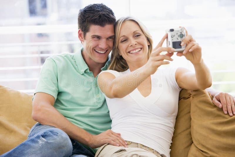 Pares na sala de visitas com câmara digital foto de stock royalty free