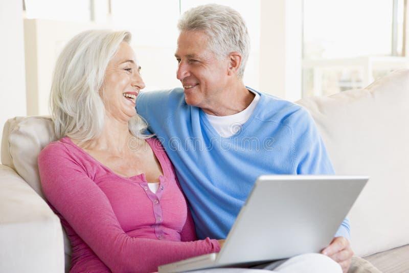 Pares na sala de visitas com sorriso do portátil imagens de stock royalty free