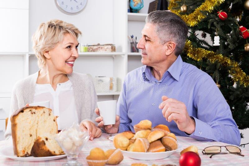 Pares na tabela que comemora o Natal e o ano novo em casa fotos de stock