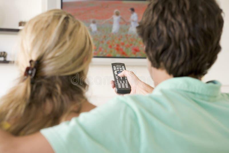 Pares na televisão de observação da sala de visitas fotografia de stock