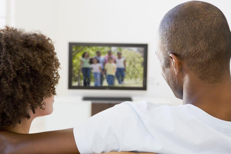 Pares na televisão de observação da sala de visitas foto de stock royalty free