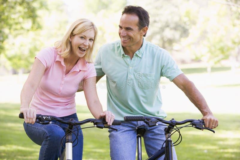 Pares nas bicicletas que sorriem ao ar livre fotografia de stock royalty free