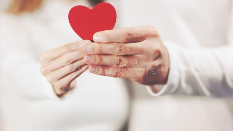 Pares nas mãos do amor que guardam a forma do coração fotografia de stock