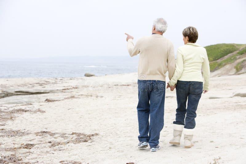 Pares nas mãos e em apontar da terra arrendada da praia fotografia de stock