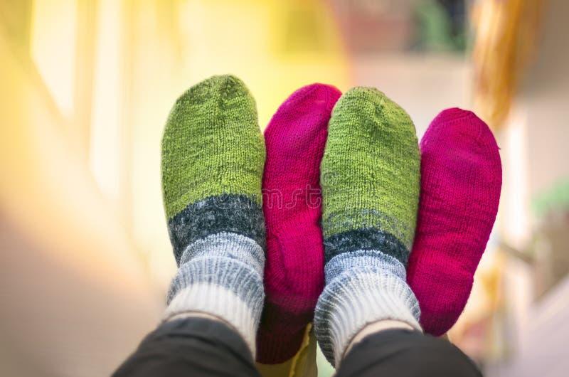 Pares nas peúgas feitas malha de lã coloridas que tocam-se em pés acima no ar Povos que relaxam em casa na esta??o fria Natal imagens de stock royalty free