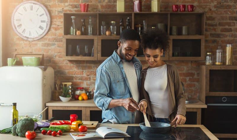 Pares negros cariñosos que preparan la comida junto en cocina moderna foto de archivo