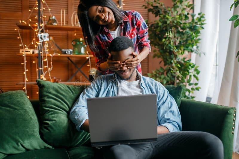 Pares negros con el ordenador port?til que se divierte en el sof? foto de archivo libre de regalías