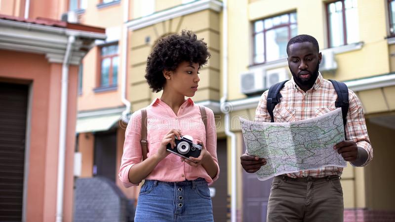 Pares negros de turistas con la cámara del mapa y de la foto, eligiendo la dirección, viaje foto de archivo
