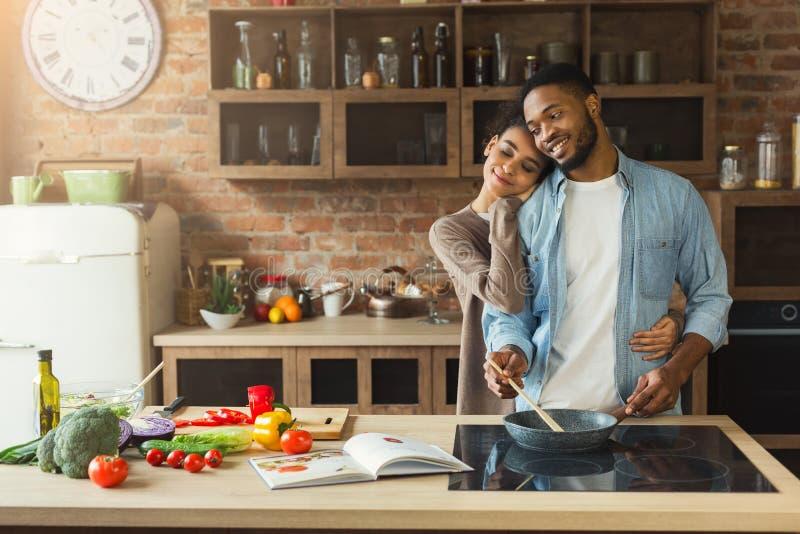 Pares negros felices que cocinan la comida sana junta fotos de archivo