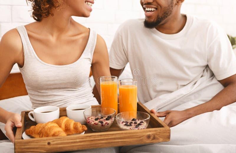 Pares negros felices que gozan del desayuno en cama imagenes de archivo