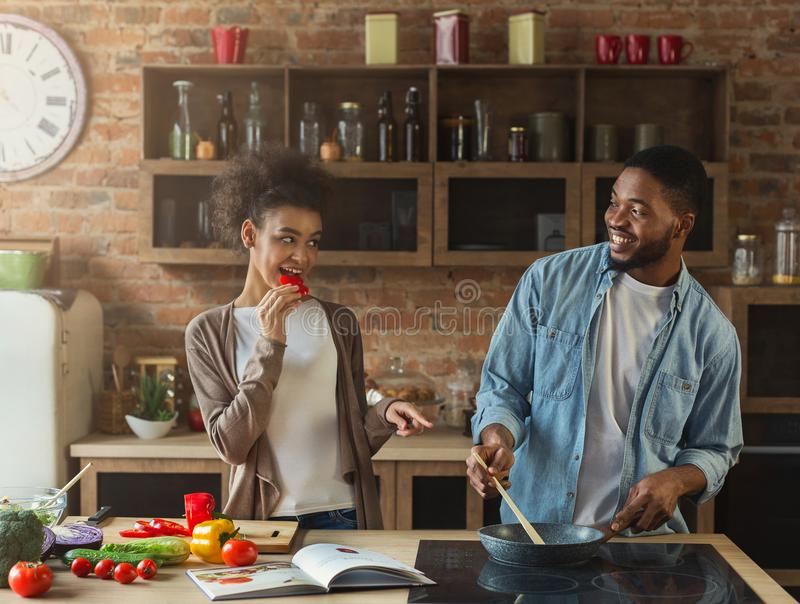 Pares negros felices que preparan la cena junto en cocina moderna fotos de archivo libres de regalías