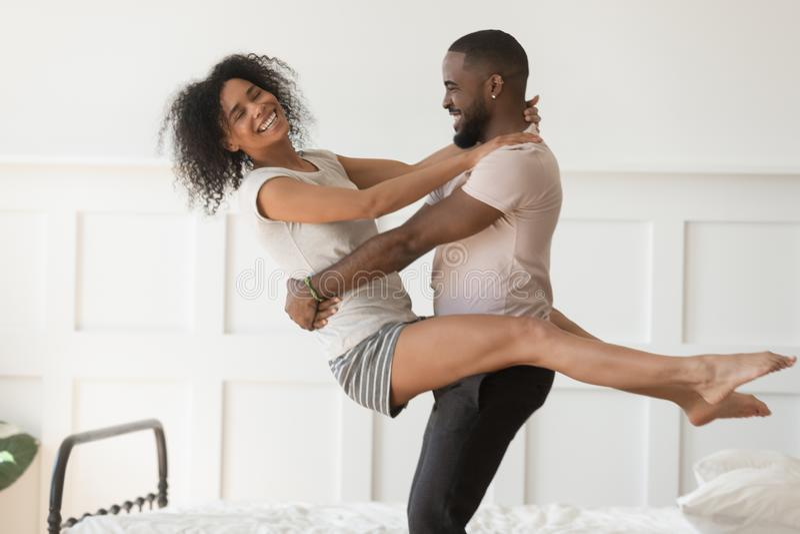 Pares negros jovenes atractivos felices que se divierten que ríe en dormitorio imagenes de archivo