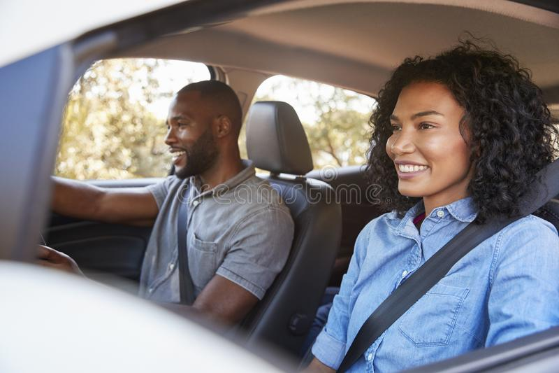 Pares negros jovenes en coche en una sonrisa del look ahead del viaje por carretera fotografía de archivo