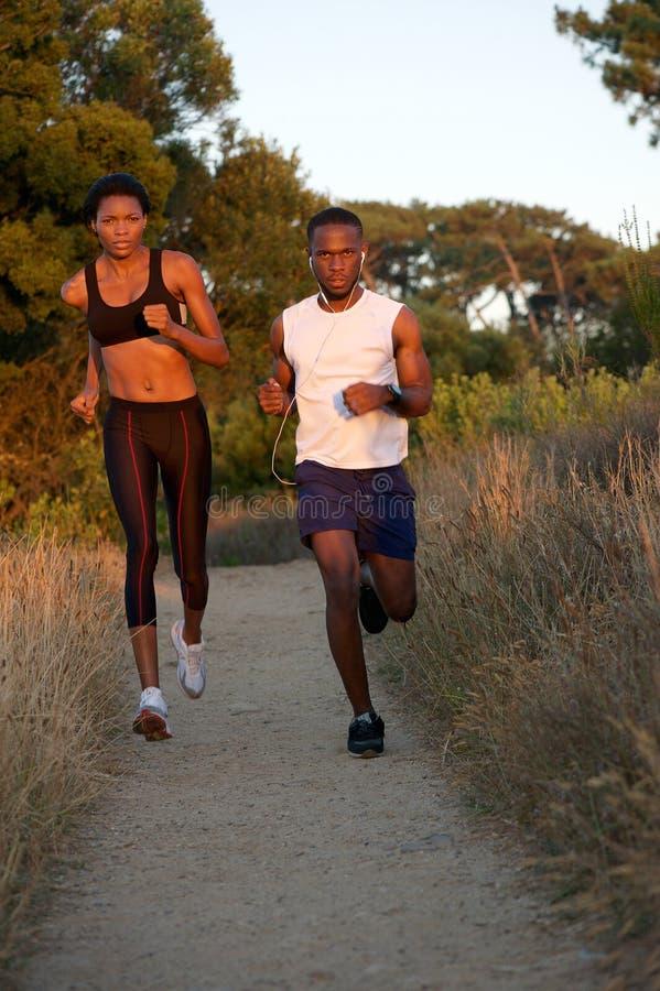 Pares negros jovenes sanos que corren junto al aire libre imagen de archivo libre de regalías