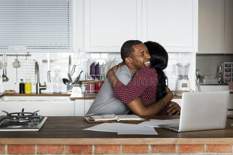 Pares negros que abrazan junto mientras que trabaja en el ordenador portátil foto de archivo libre de regalías