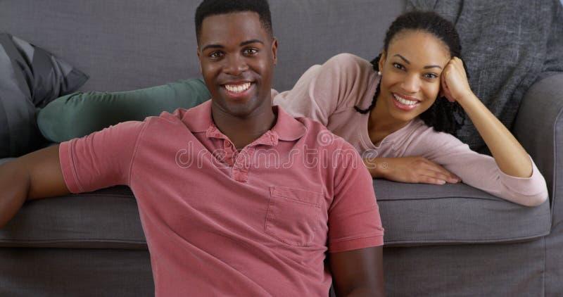 Pares negros que se relajan en el sofá y que sonríen en la cámara fotos de archivo libres de regalías
