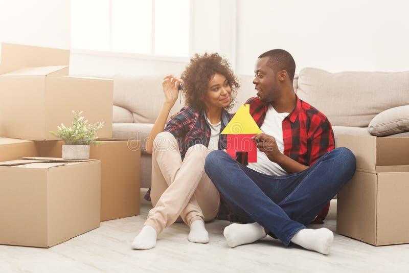 Pares negros que se sientan en piso en el nuevo apartamento imagen de archivo libre de regalías
