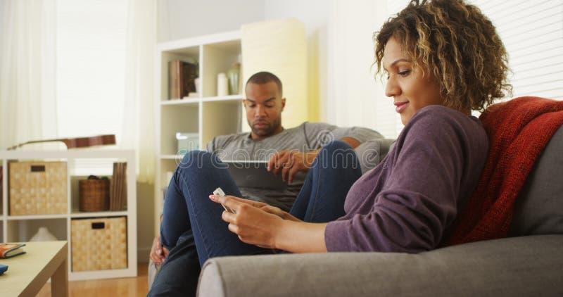 Pares negros usando los dispositivos electrónicos en el sofá imagen de archivo libre de regalías