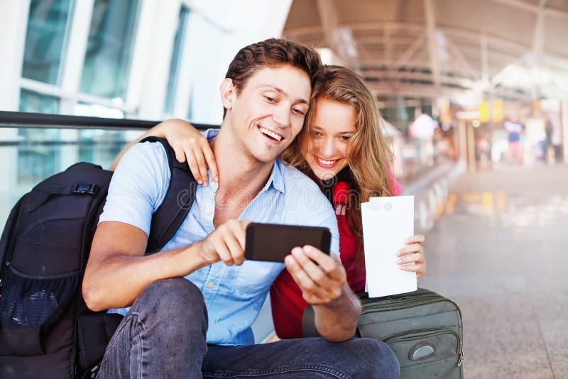 Pares no aeroporto usando o curso app foto de stock