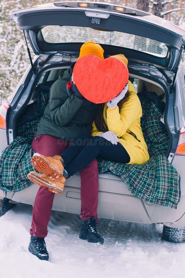 Pares no amor com o coração vermelho grande que senta-se em um carro com um tronco e um beijo abertos imagens de stock royalty free