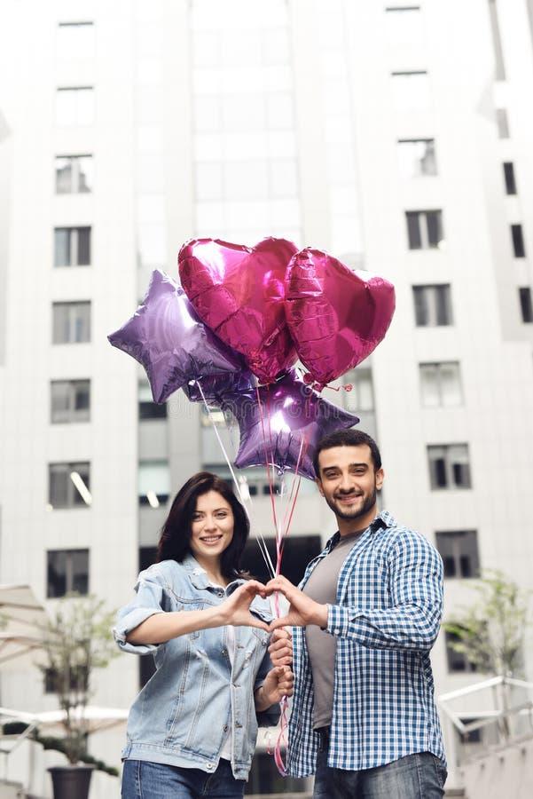 Pares no amor com os balões que unem as mãos fotografia de stock royalty free
