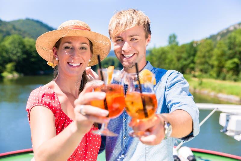 Pares no amor em coctails bebendo do cruzeiro do rio no verão imagem de stock