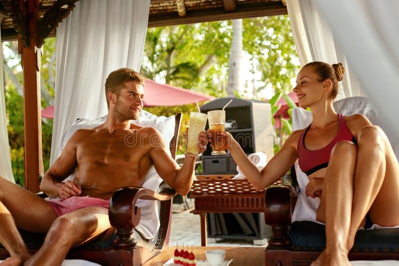 Pares no amor em férias românticas com os cocktail em termas foto de stock