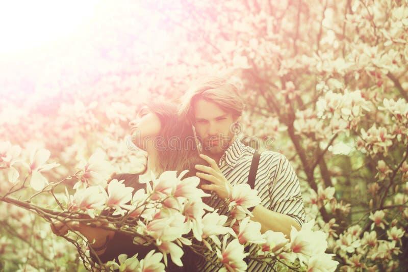 Pares no amor, no homem e na menina apreciando a flor da flor da magnólia imagens de stock